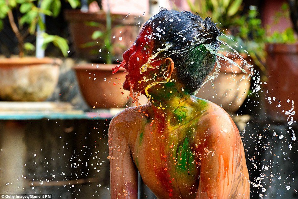 This boy tries to wash off the colour splashed onto him during Holi. People apply oil on to their skin to make the colour removal easier