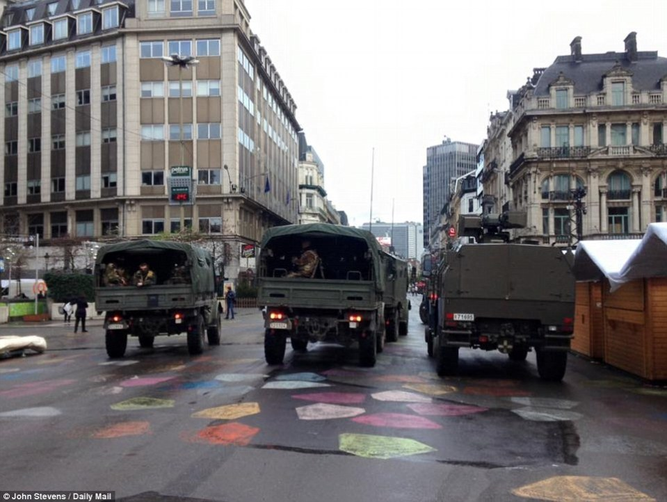 High alert: Trucks filled with army personnel take up positions inside the heart of the Belgian capital