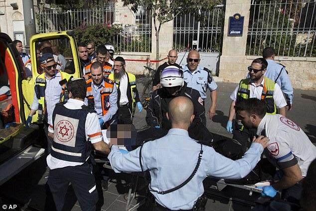 Llevaron: Medics evacuar el cuerpo de un adolescente palestino, nombrado como Hadeel Wajih Awad, disparó en la calle, donde la policía dice que apuñaló a un hombre en el mercado Mahane Yehuda, en el centro de Jerusalén