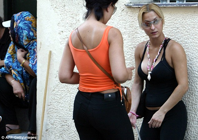Greek prostitutes argue during a protest held by more than 50 prostitutes in front of a brothel in Athens 04 August 2003. Athens municipality had threatened to shut down at least 15 brothels for being too close to churches and schools