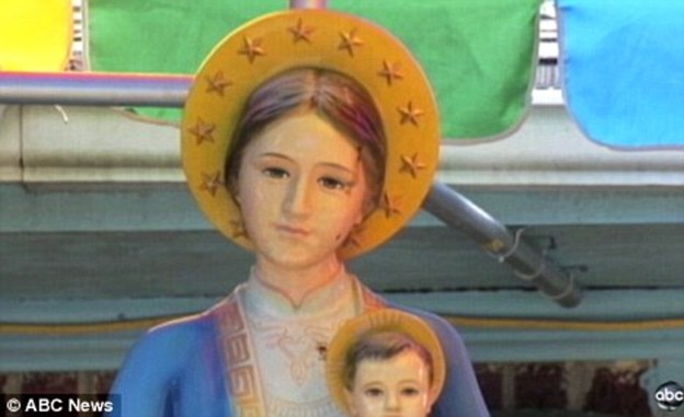 The statue of the Mother Mary holding baby Jesus is in the front garden of a home in Baton Rouge