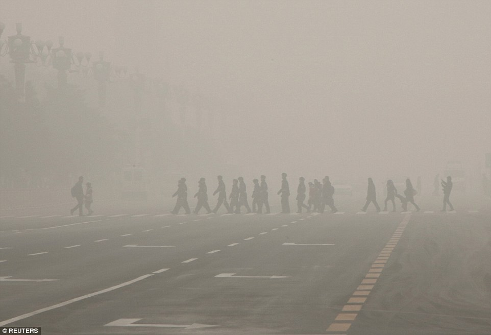 Smog: Pedestrians and a policeman cross the street in Tiananmen Square, in Beijing, China, aspollution soared above healthy limits