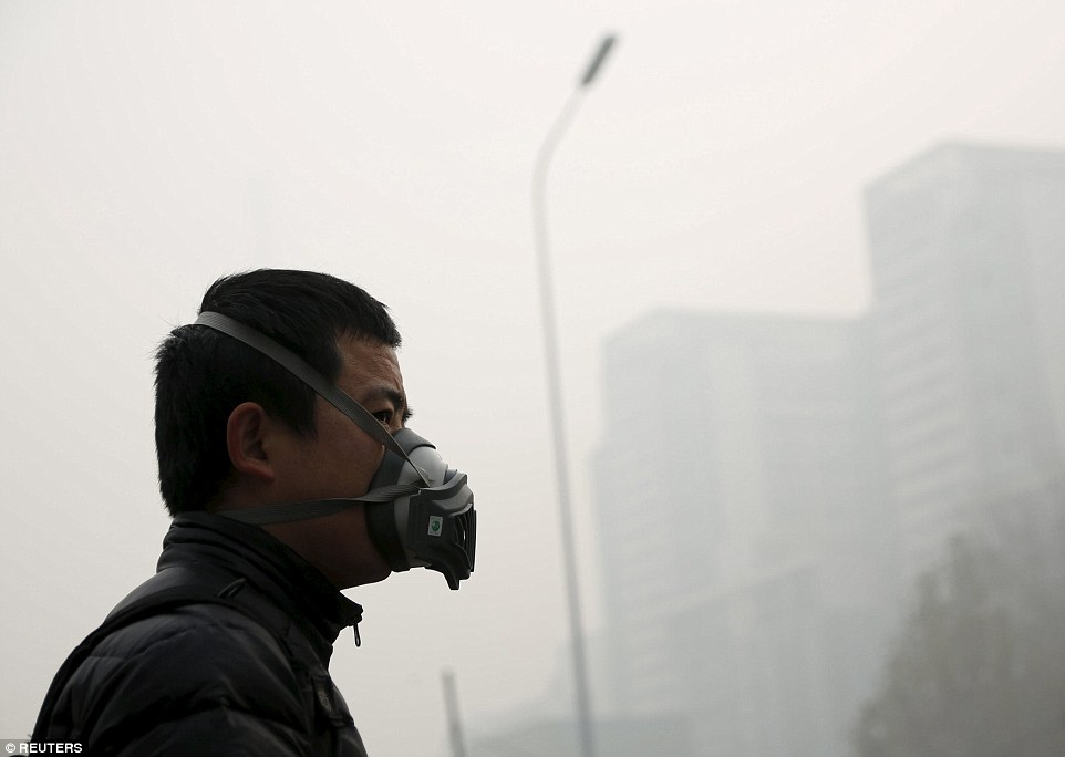 Protection: A man wearing a mask walks through China's capital, Beijing, as a blanket of hazardous, choking smog covering the city