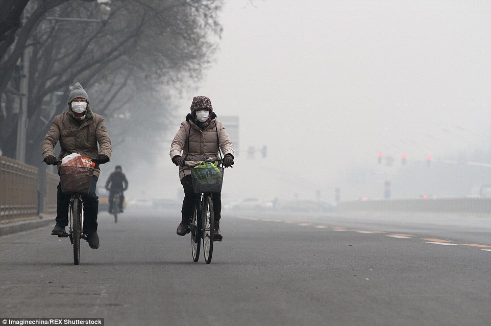 Cyclists wearing face masks ride through heavy smog in Beijing. Chinese President Xi Jinping is among some 150 leaders at COP21 today
