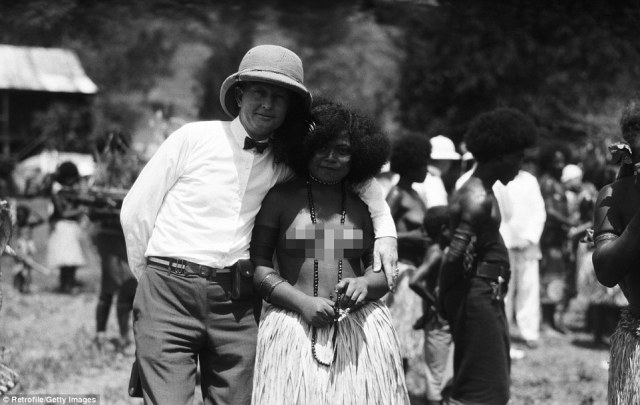 A male tourist wearing pith helmet poses with a topless local woman in Port Moresby, Papua New Guinea, in the 1920s