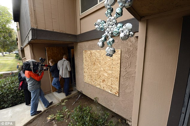 Farook and Malik died in a shootout with police hours after the massacre in San Bernardino on Wednesday. Above, media and neighbors enter their boarded-up apartment