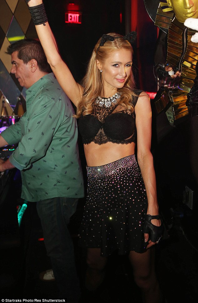 Purrr-fectly lovely: Paris Hilton donned pussy cat ears as she showed off her taut and toned tummy in a black lacy bra-style top for her DJ gig at Wall Lounge in Miami's W Hotel during Art Basel on Friday evening