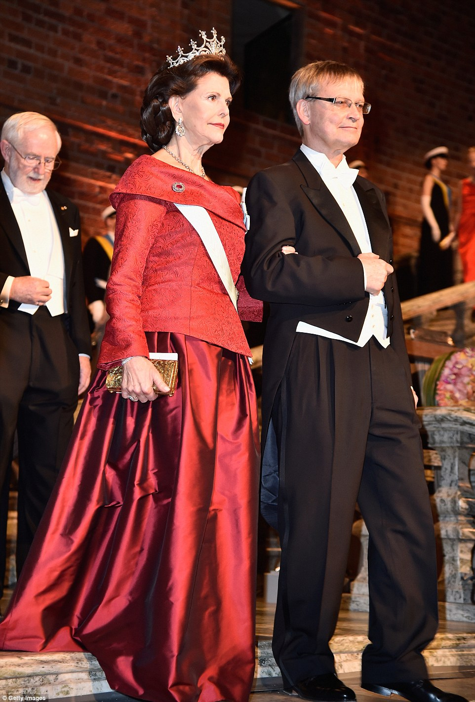 Queen Silvia was resplendent in red and her tiara encrusted with 500 diamonds; she was escorted by Professor Carl-Henrik Heldin, a Swedish molecular biologist and vice president of the European Research Council