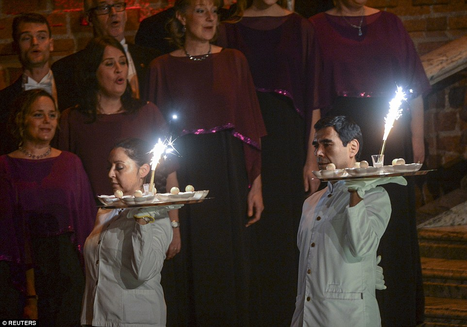Waiters arrive with spectacular desserts at the the event holding them aloft as they walk through the grand hall