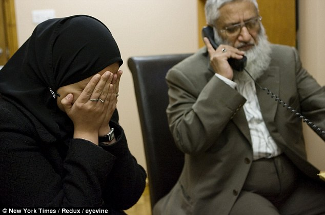 A distraught wife seeking a divorce at a Sharia Court in London holds her head in her hands as she sits with judge Suhaib Hasan