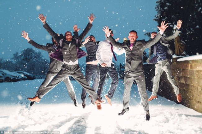 Carly said that the snow began settling at the beginning of their ceremony and by the time they had finished eight inches had fallen. Pictured: Male guests jump around in the powder