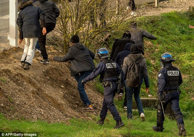 French police forces attempt to disperse migrants and refugees on one of the roads of the Eurotunnel in Calais