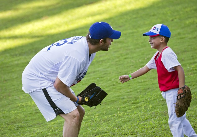 Los Angeles Dodgers pitcher Clayton Kershaw, from the U.S., speaks with a young baseball player during a MBL baseball clinic in Havana, Cuba, Wednesday, Dec....