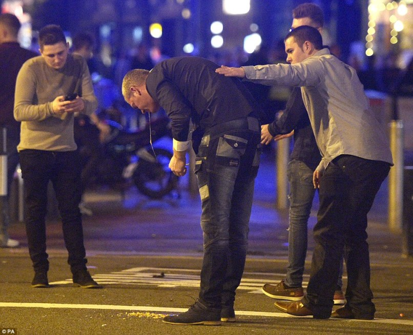 Unwell: A man is comforted by his friends as he is sick in St Mary Street in Cardiff during the biggest night out of the year