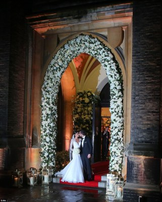 Picture perfect: The bride and groom could barely take their eyes off each other as they posed under a beautiful floral decorated archway