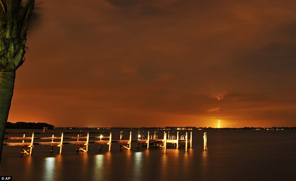 The SpaceX Falcon 9 launch appears in the distance from the back of River Rocks dockside restaurant along the Indian River, south of Rockledge, Florida