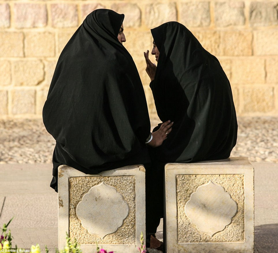 Two young women gossip and share a secret while relaxing in the sunshine in Shiraz