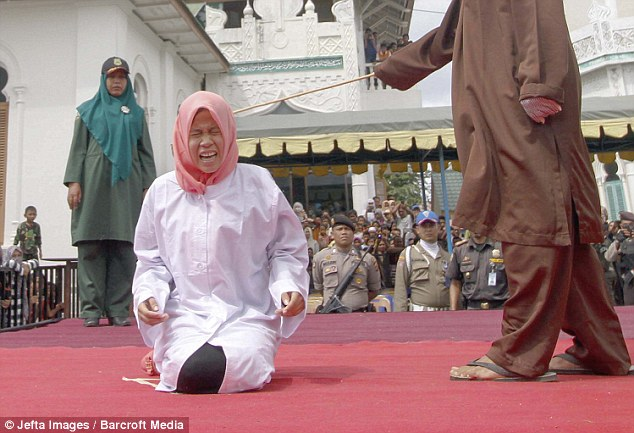 She screams out in agony after being whipped in a caning ceremony outside a mosque in Indonesia's Banda Aceh region