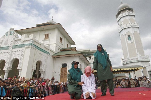 The woman is brought to the stage by two female members of the Sharia Police and is put in position on her knees