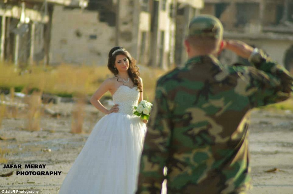 A remarkable backdrop: Behind the couple, buildings stood abandoned and partially blown apart, while rubble littered the dusty ground