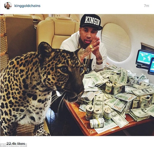 He's roaring: Tyga shared an Instagram snap on Thursday of himself with a leopard and loads of cash