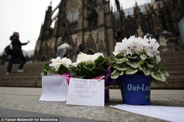 Manhunt: At least 12 more people are being sought in connection with 121 complaints from women attacked on the last night of the year (pictured, flowers left at the scene of the mass attack)