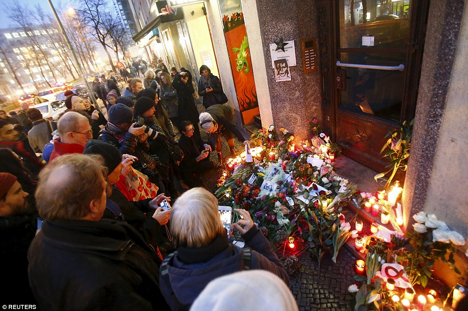 Gathering: Fans photographing the display outside Bowie's Berlin flat after a day of tributes
