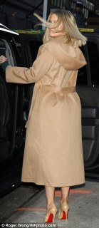 Covetable coat: Khloe's outerwear added an elegant and cosy touch to her look, a long camel coat with a hood and belt