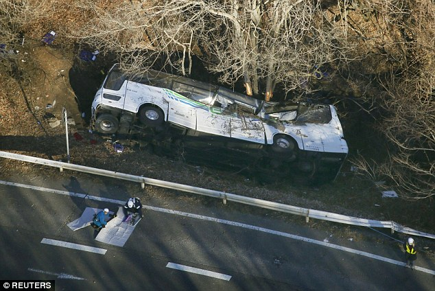 A tour bus that veered off a road is seen after it crashed in Karuizawa, Nagano prefecture in Japan