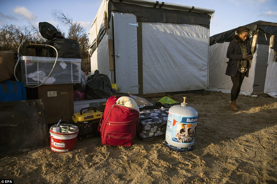 A woman stands next to her belongings waiting for them to be moved after being told to leave part of the 'Jungle' camp in Calais