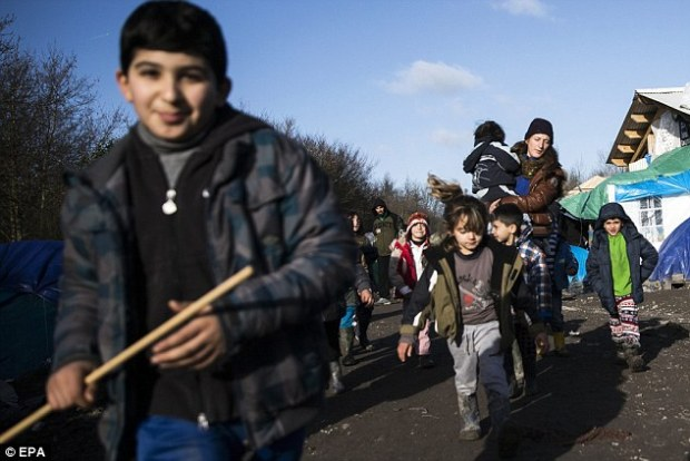 Kurdish children play as they get out of the volunteer school in the makeshift migrant camp in Grande-Synthe