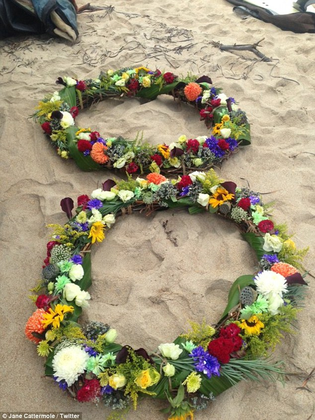 Floral wreaths and brightly coloured flowers were taken to the beach on Sunday while a tribute table was set up next to cars in the parking lot of Secret Harbour