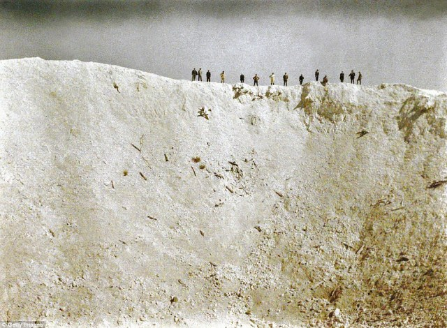 This dramatic photograph shows soldiers standing on a ridge above a crater 45m deep created by mines placed by British forces underneath German positions near Messines in West Flanders on 7 June 1917. Some 10,000 soldiers died in the bla