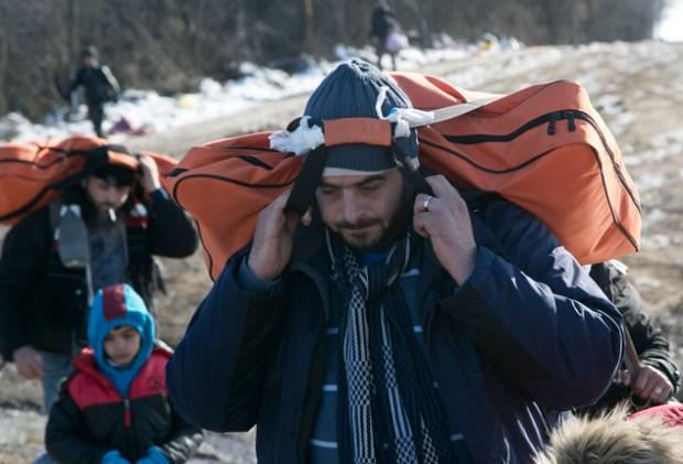 Desperate: Migrants carrying their belongings on their backs search for a new life in Europe