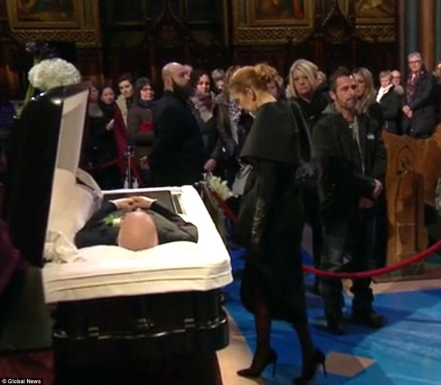 A prayer before the last farewell: The singing sensation approached the open casket with her head down and wearing a black coat, gloves and pumps