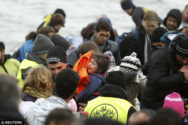 A young girl cries as she is carried through a crowd after arriving on Lesbos on Friday. Officials at the meeting simultaneously said they do not want to 'downplay' the problems
