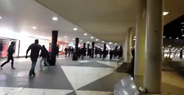Mob of black-clad masked men went on a rampage in and around Stockholm's main train station targeting refugee children