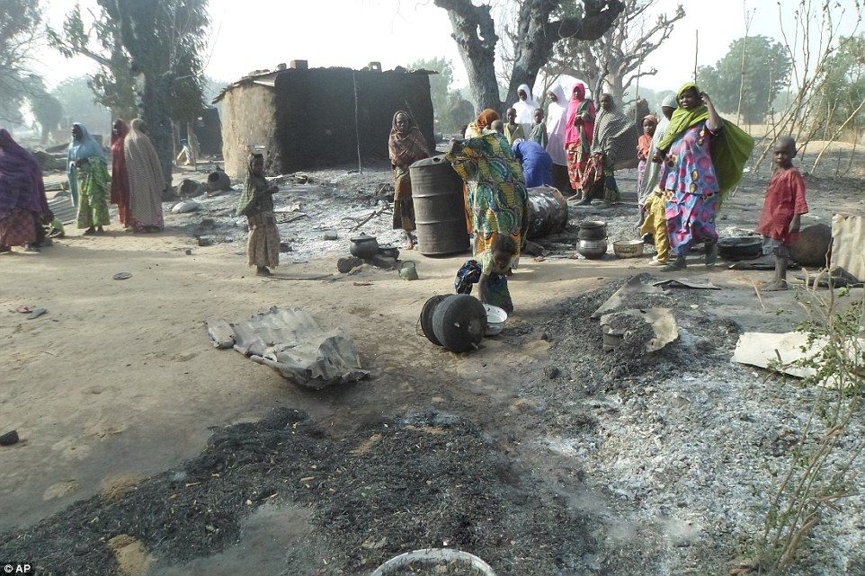 Devastated: Women and children search through debris in the village of Dalori after it was burnt to the ground by Boko Haram extremists