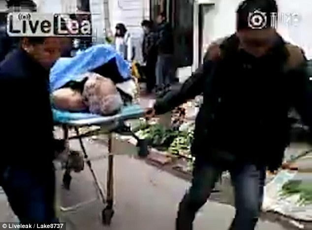 Men transport the alleged dead body with the woman still on top out of a building on a hospital stretcher
