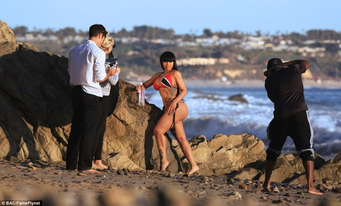 Centre of attention: The star was perfectly at ease as she struck a series of sultry poses up against a rock