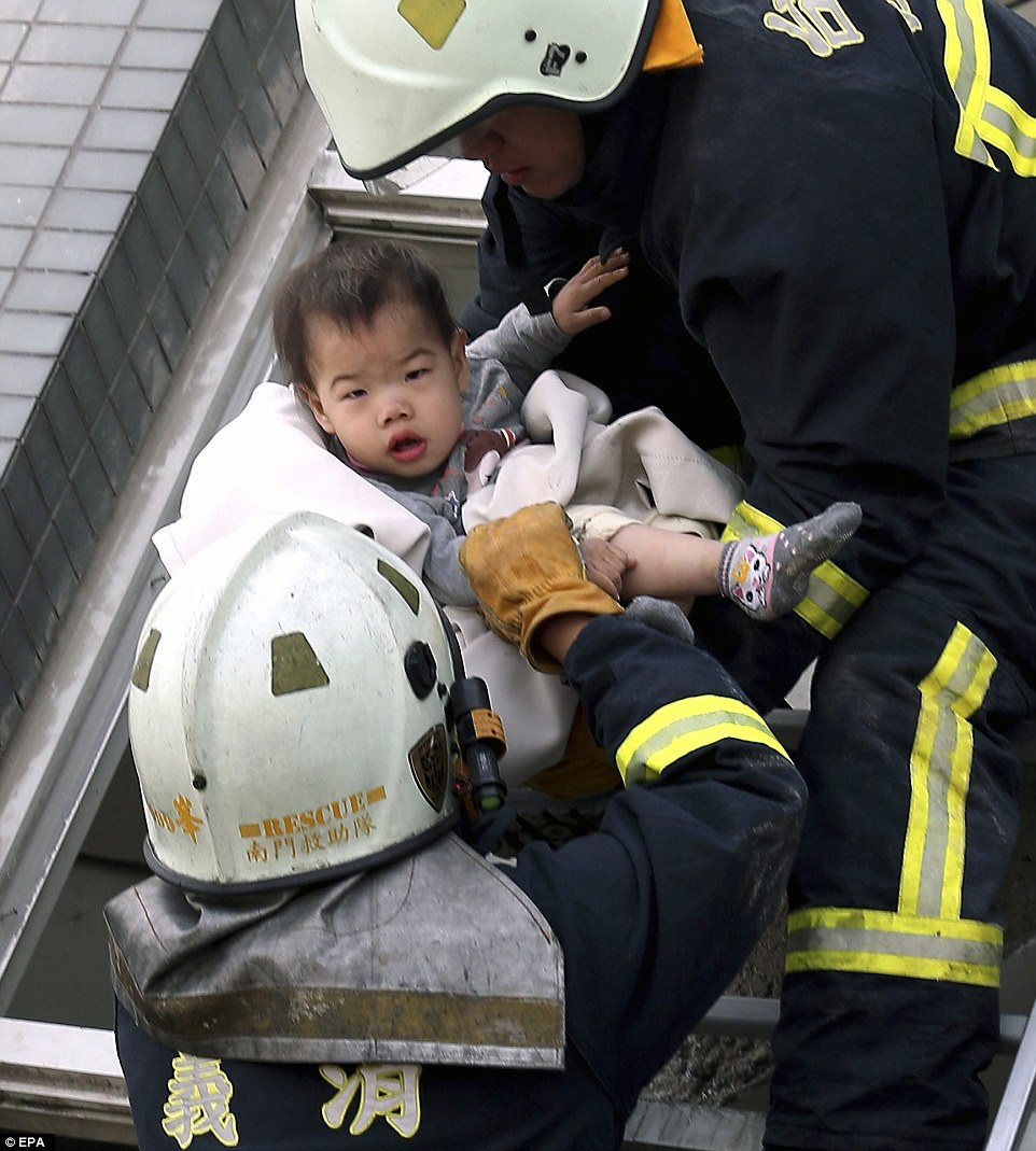 Alive: Fire crews are pictured pulling a stunned infant from the wreckage of a 17-storey apartment building in the city of Tainan, Taiwan, after an earthquake struck this morning killing three and leaving hundreds more trapped