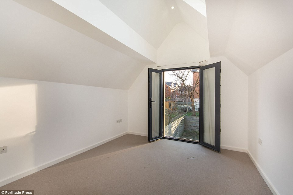 Upstairs: There are two bedrooms on the top floor. This one looks out onto the garden, in a residential area in East Dulwich