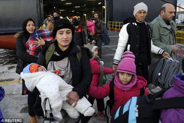 Arrivals: Refugees and migrants such as this group, who arrived aboard the passenger ferry at the port of Piraeus, near Athens, Greece, on Sunday, would be forced to return