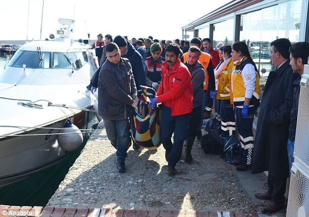 Los hombres llevan el cuerpo de una persona que murió cuando el barco, llevando a 40 personas, se hundió en el mar Egeo hoy