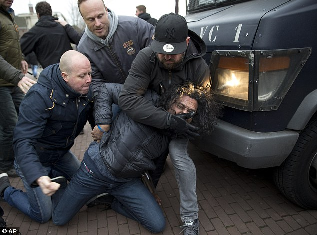 Violence: Police officers wrestle a man to the ground during the Pegida demonstration in Amsterdam