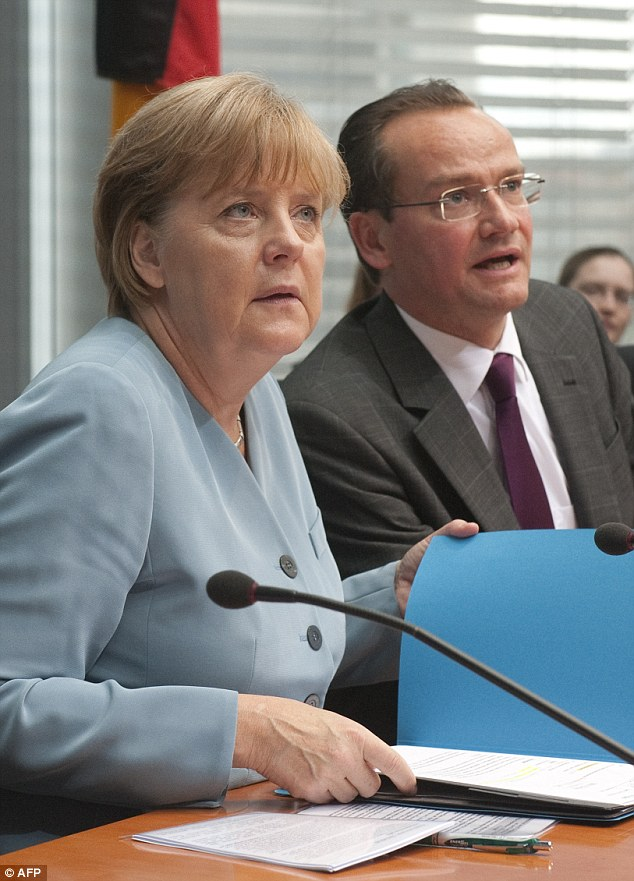 Close ally: German Chancellor Angela Merkel (L) sits next to chairman of the parliamentary commission charged with EU affairs Gunther Krichbaum (R)