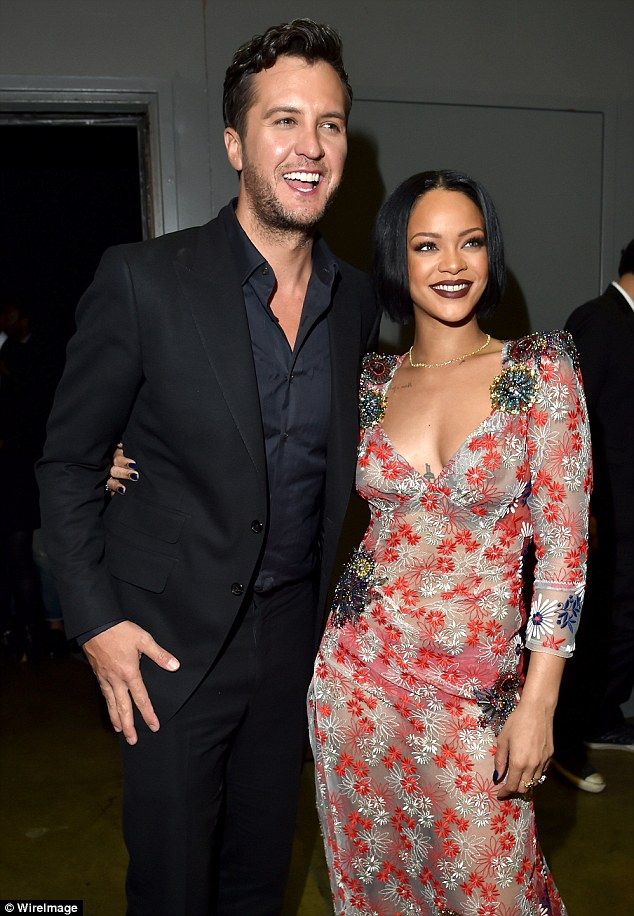 Looking good! The Bajan beauty flashed her underwear in the sheer frock as she posed alongside country star Luke Bryan