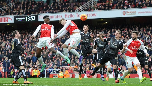Welbeck (second left) scores a last gasp header to hand Arsenal a dramatic 2-1 victory over Leicester and close the gap at the top