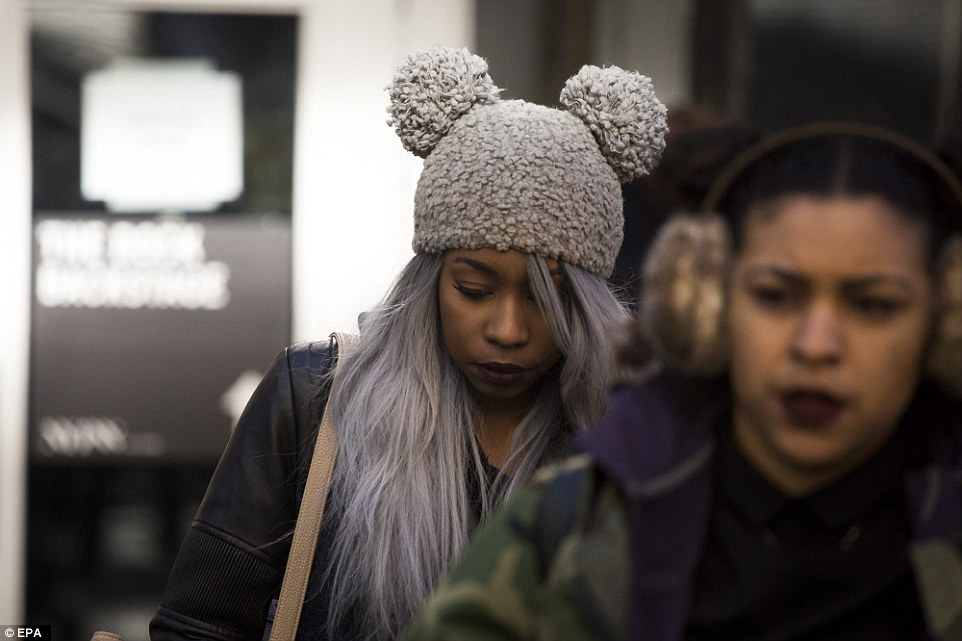 A woman wears a fashionable hat as she braces against the cold in New York City