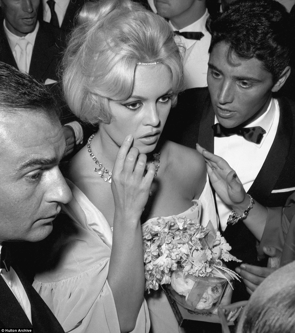 French actress Brigitte Bardot with her partner, the french jazz guitarist Sasha Distel, in 1958. The extravagant star is surrounded by men in tuxedos